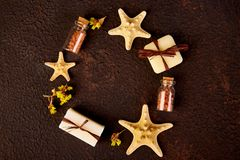 Spa concept. Aromatic candles, soap beauty and Spa cosmetic. Products, salt, starfish on brown table. Flat lay Stock Photo