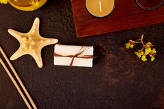 Spa concept. Aromatic candles, soap beauty and Spa cosmetic. Products, salt, starfish on brown table. Copy space Flat lay Stock Image