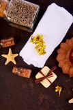 Spa concept. Aromatic candles, soap beauty and Spa cosmetic. Spa concept. Aromatic candles, towel, soap beauty and Spa cosmetic products, salt, starfish on brown Stock Photography