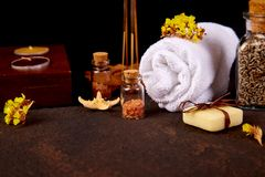 Spa concept. Beauty. Spa concept. Aromatic candles, towel,  soap beauty and Spa cosmetic products, salt, starfish on brown table Royalty Free Stock Photography