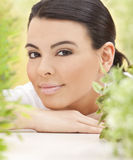 Spa Concept Beautiful Hispanic Woman Smiling. Surrounded in natural green leaves Stock Photos