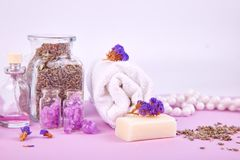 Spa concept. Beauty. Spa concept. Aromatic candles on purple table. Beauty and Spa cosmetic products, salt, lavender, towel Stock Photo