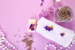 Spa concept. Aromatic candles, soap beauty and Spa cosmetic. Spa concept.  Beauty and Spa cosmetic products, salt, towel, soap on purple  table. Flat lay. Copy Royalty Free Stock Photography