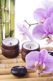 Spa, conceptual composition. Spa concept with black massage stones, purple orchid flower and bamboo leaves and some aromatic candles Stock Photos