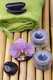 Spa, conceptual composition. Spa concept with black massage stones, purple orchid flower and bamboo leaves and some aromatic candles Royalty Free Stock Photos