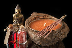 Spa concept. Buddha statue, essential oil, sea salt and aromatic sticks Stock Image