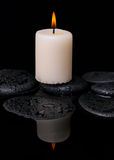 Spa concept of candle on zen stones with drop Royalty Free Stock Images