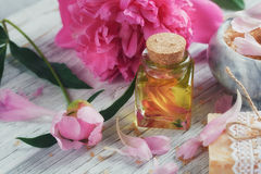 SPA concept: composition of spa treatment with natural sea salt,. Aromatic oil and peonies flowers on white wooden background Stock Photography