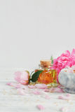 SPA concept: composition of spa treatment with natural sea salt,. Aromatic oil and peonies flowers on white wooden background Stock Images