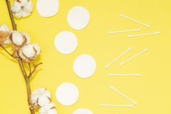 Spa concept. Flat lay background with cotton branch, cotton pads, eared sticks. Cotton Cosmetic Makeup Removers Tampons. Hygienic sanitary swabs on the yellow stock images