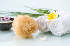 Spa concept with Floating Flowers, Loofah, and towel Royalty Free Stock Image