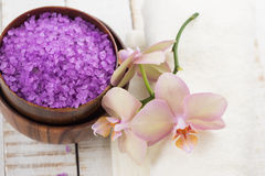 Spa concept. Flowers, sea salt  and towel on white wooden backgr Stock Photo