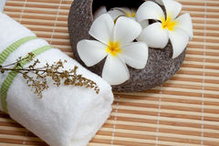 Spa Concept: Frangipani flowers, white towel. On bamboo mats stock photos