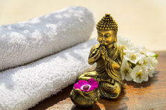 Spa Concept with golden Buddha. Spa concept with Buddha, towels, flowers and wood Royalty Free Stock Photo