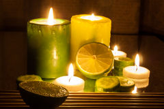 Spa Concept- Green and Yellow lit candles, Slice of lemon. Green and Yellow lit candles, Slice of lemon. Spa concept Royalty Free Stock Photography