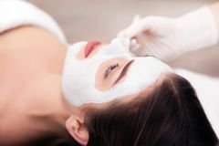 Spa concept. Hand applying nourishing mask on female face in spa salon.  Royalty Free Stock Image