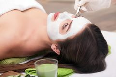 Spa concept. Hand applying nourishing mask on female face in spa salon.  Stock Images