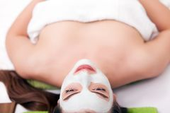 Spa concept. Hand applying nourishing mask on female face in spa salon.  Royalty Free Stock Photography