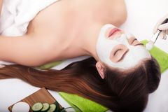 Spa concept. Hand applying nourishing mask on female face in spa salon.  Stock Photo