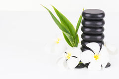 Spa concept with hot stones, green leaves and Frangipani flowers Royalty Free Stock Images