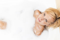 Spa Concept and Ideas. Young Caucasian Blond Female having Relaxation Bathtub with Foam. Royalty Free Stock Photos