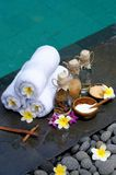 At the Spa. Concept in a luxury Villa on Bali Island with, Massage oil, bath-salt, Volcanics stones, body scrub, Towels,Cinnamon sticks, Orchids and frangipani Royalty Free Stock Images