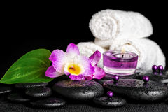 spa concept of orchid flower, zen basalt stones with drops, purple candles, beads and white towels, closeup stock photos