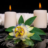 Spa concept of passiflora flower, green leaf with drop, towels a. Nd candles on zen stones in ripple reflection water, closeup royalty free stock photos