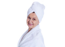 Spa concept portrait. Aged good looking woman with white towel on her headCity background made of many building silhouettes Stock Image