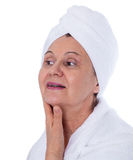 Spa concept portrait. Aged good looking woman with white towel on her headCity background made of many building silhouettes Royalty Free Stock Image