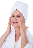 Spa concept portrait. Aged good looking woman with white towel on her headCity background made of many building silhouettes Stock Photos
