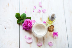 Spa concept with pot of moisturizing cream beautiful pink roses and rose essence oil on white wooden background Spa treatment. Royalty Free Stock Photos