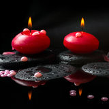 Spa concept of  red candles and pearl beads on zen stones Stock Photos
