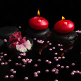 Spa concept of red candles, zen stones with drops, orchid Royalty Free Stock Image
