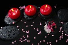 Spa concept of red candles on zen stones with drops, orchid Stock Photos