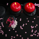 Spa concept of red candles on zen stones with drops, orchid Royalty Free Stock Image