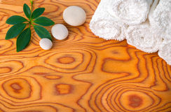 Spa concept of rolled white towels, stones and green leaf on roo Stock Image