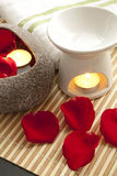 Spa Concept: Rose petals, aroma candles. On bamboo mats Stock Photos