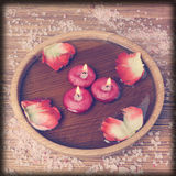 Spa concept with rose petals, salt and burning candles that floa Stock Images