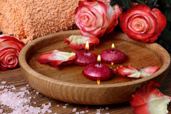 Spa concept with roses, pink salt and candles that float in wate Royalty Free Stock Images