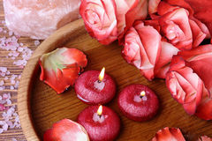 Spa concept with roses, pink salt and candles that float in wate Royalty Free Stock Photo