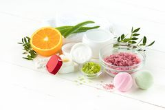 Spa concept with salt, mint, lotion, towel on white background. Spa concept with salt, mint, lotion, towel on white wooden background stock photos