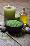 Spa concept. Sea salt in stone bowl with candle and herbal soap Stock Photos