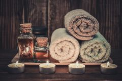 Spa concept. Towels with  massage oil in vintage bottle, candles and stones for stone massage on wooden background Royalty Free Stock Images