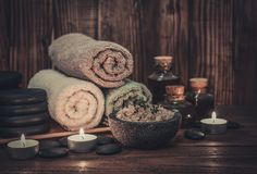 Spa concept. Towels with sea salt, massage oil in vintage bottle, candles and stones for stone massage on wooden background Stock Images