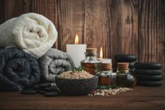 Spa concept. Towels with sea salt, massage oil in vintage bottle, candles and stones for stone massage on wooden background Stock Photography