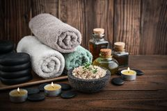Spa concept. Towels with sea salt, massage oil in vintage bottle, candles and stones for stone massage on wooden background Royalty Free Stock Images