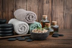 Spa concept. Towels with sea salt, massage oil in vintage bottle, candles and stones for stone massage on wooden background Royalty Free Stock Photography