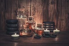 Spa concept. Towels with sea salt, massage oil in vintage bottle, candles and stones for stone massage on wooden background Royalty Free Stock Image
