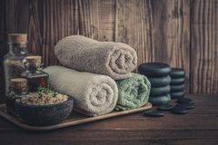 Spa concept. Towels with sea salt, massage oil in vintage bottle, candles and stones for stone massage on wooden background Royalty Free Stock Photo